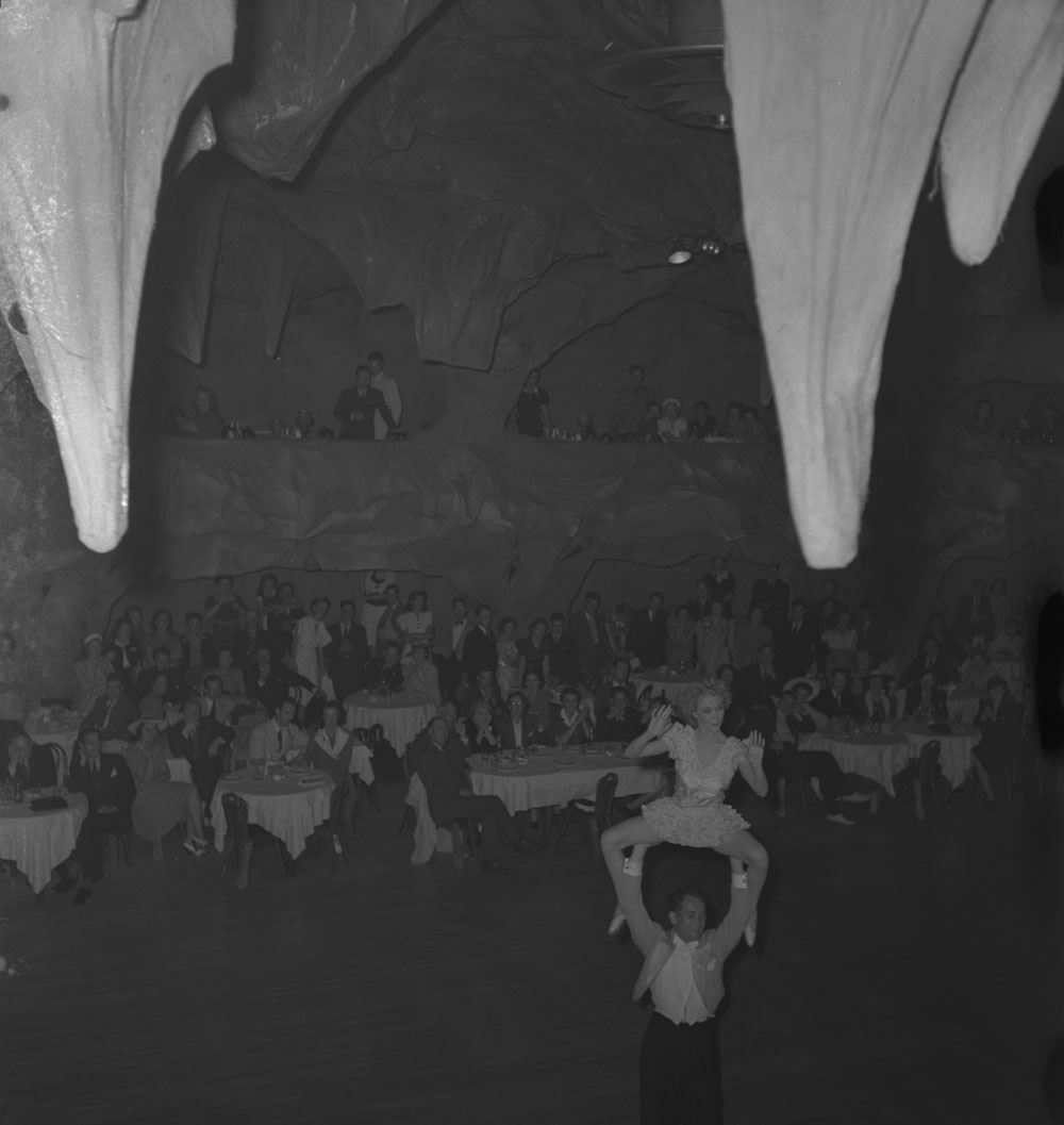 Large group watching unidentified performers at the Cave Supper Club